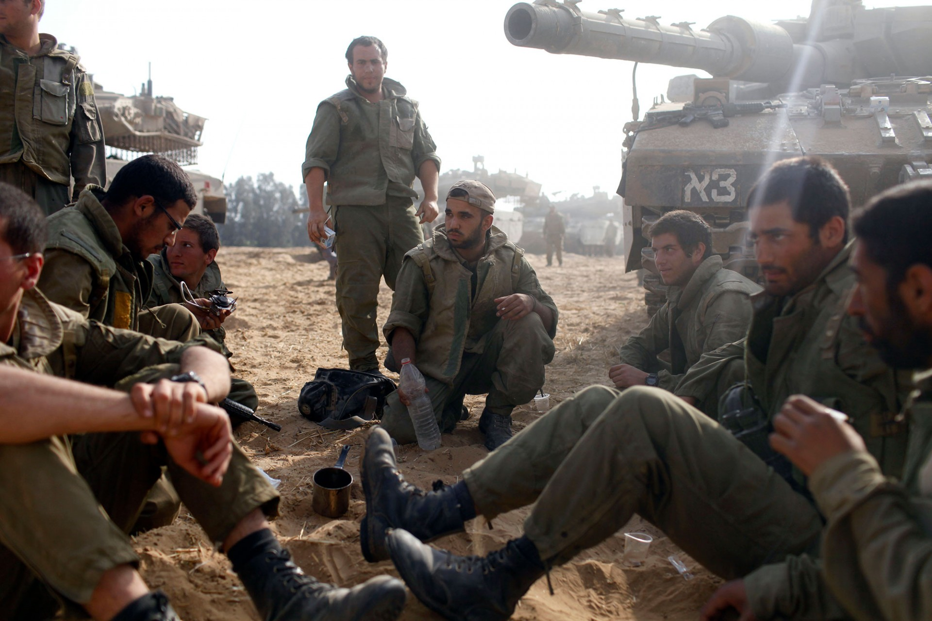 Israeli soldiers sit next to a tank in a deployment area on August 02, 2014 on Israel's border with the Gaza Strip.