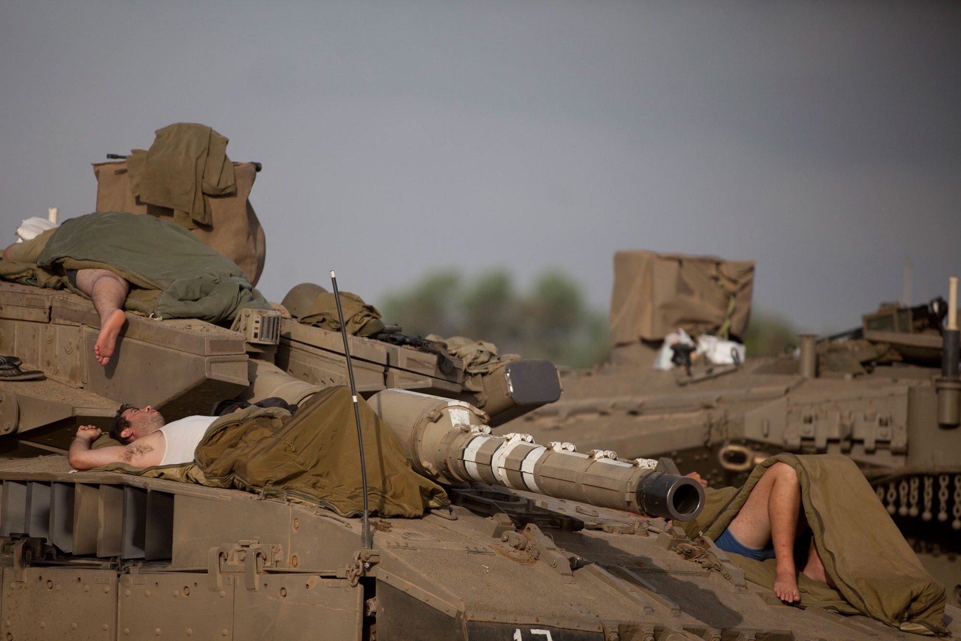 Israeli soldiers sleep on a tank in a deployment area on July 13, 2014 on Israel's border with the Gaza Strip.