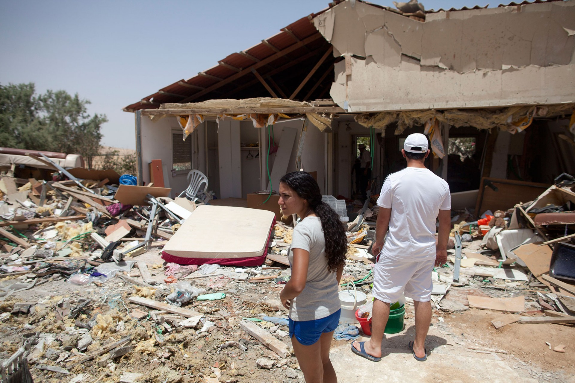 An Israeli woman inspects the damage of a house after it was hit by a rocket fired from Gaza on July 12, 2014 in Beer Sheva , Israel.