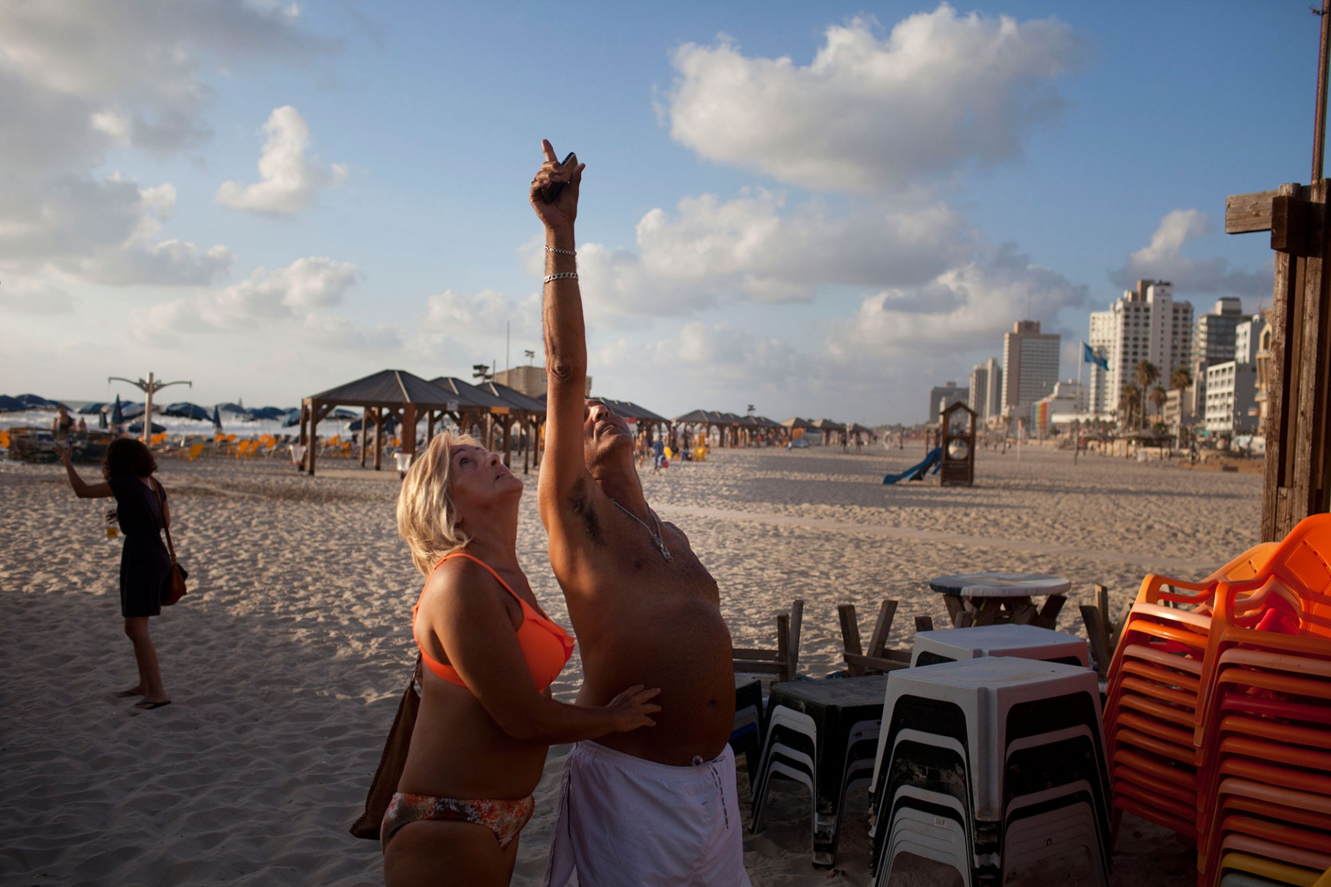 Israelis and tourists watch the sky on the beach during a rocket attack fired by Palestinian militants from the Gaza Strip on July 15, 2014 in Tel Aviv, Israel.