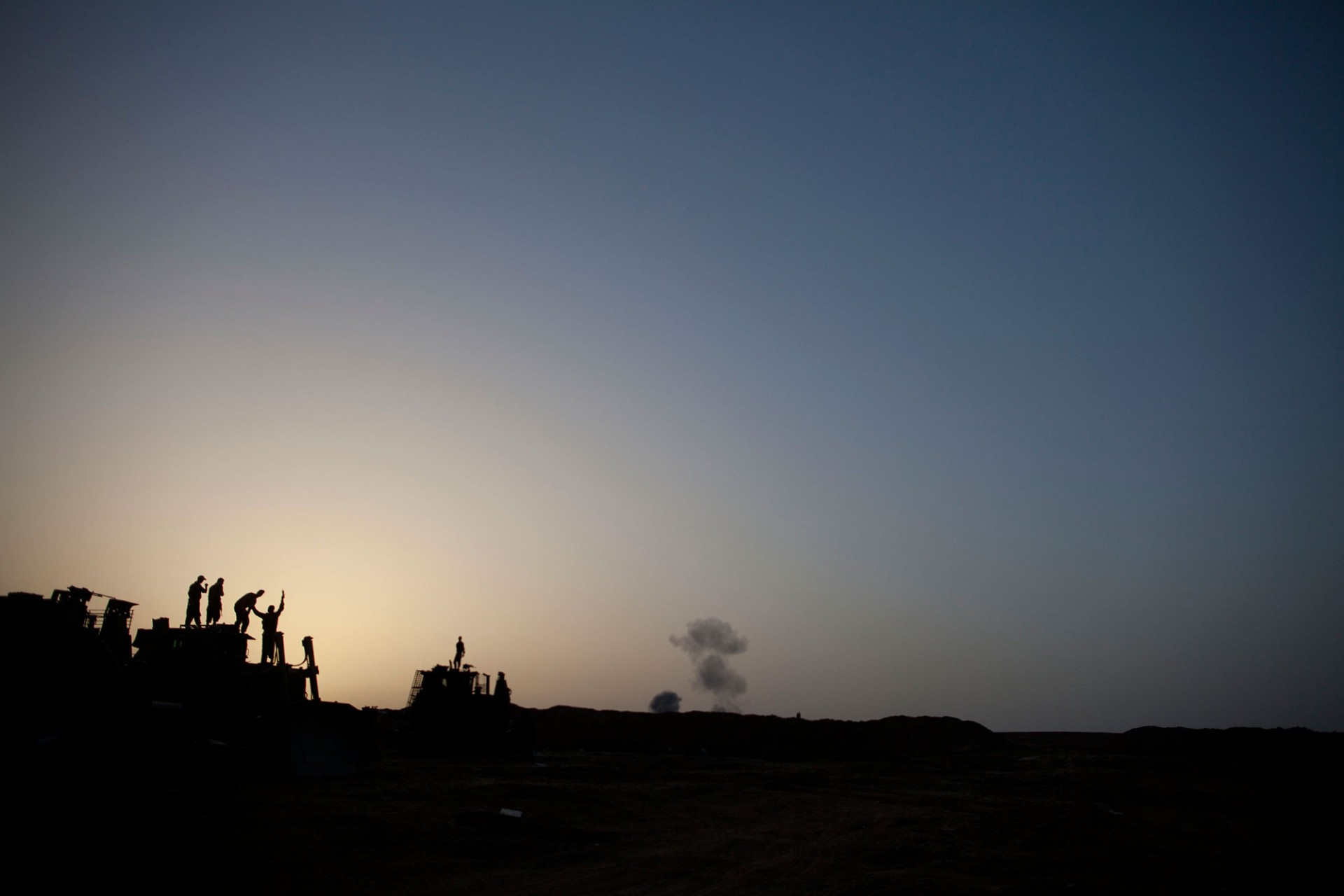 Israeli soldiers watch smoke plumes rises from Gaza following an Israel Air Force bombing on July 12, 2014 in Israel Gaza border.