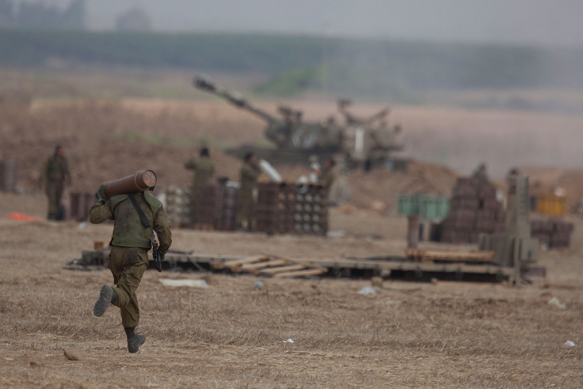 An Israeli soldier runs with shell next to artillery cannons on July 20, 2014 at the Israeli-Gaza border.