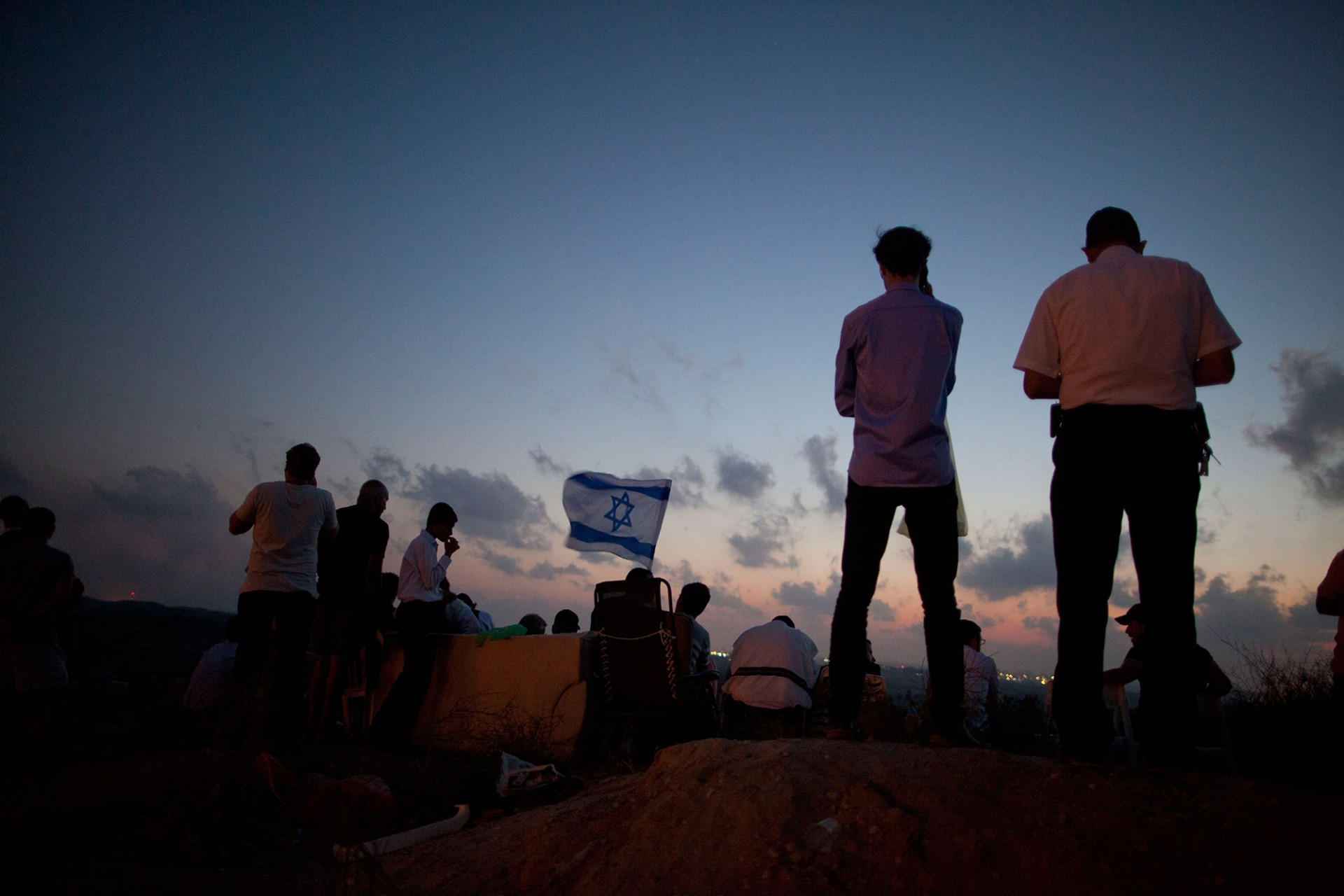 Israelis stand with an Israeli flag on a hill overlooking the Gaza Strip on July 20, 2014 near Sderot, Israel.