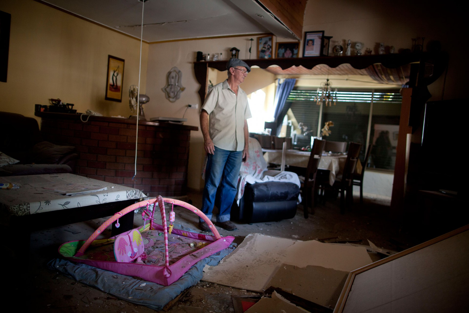 An Israeli man inspects an Israeli home allegedly hit by a Hamas rocket on July 22, 2014 in Yahud south to Tel Aviv, Israel.