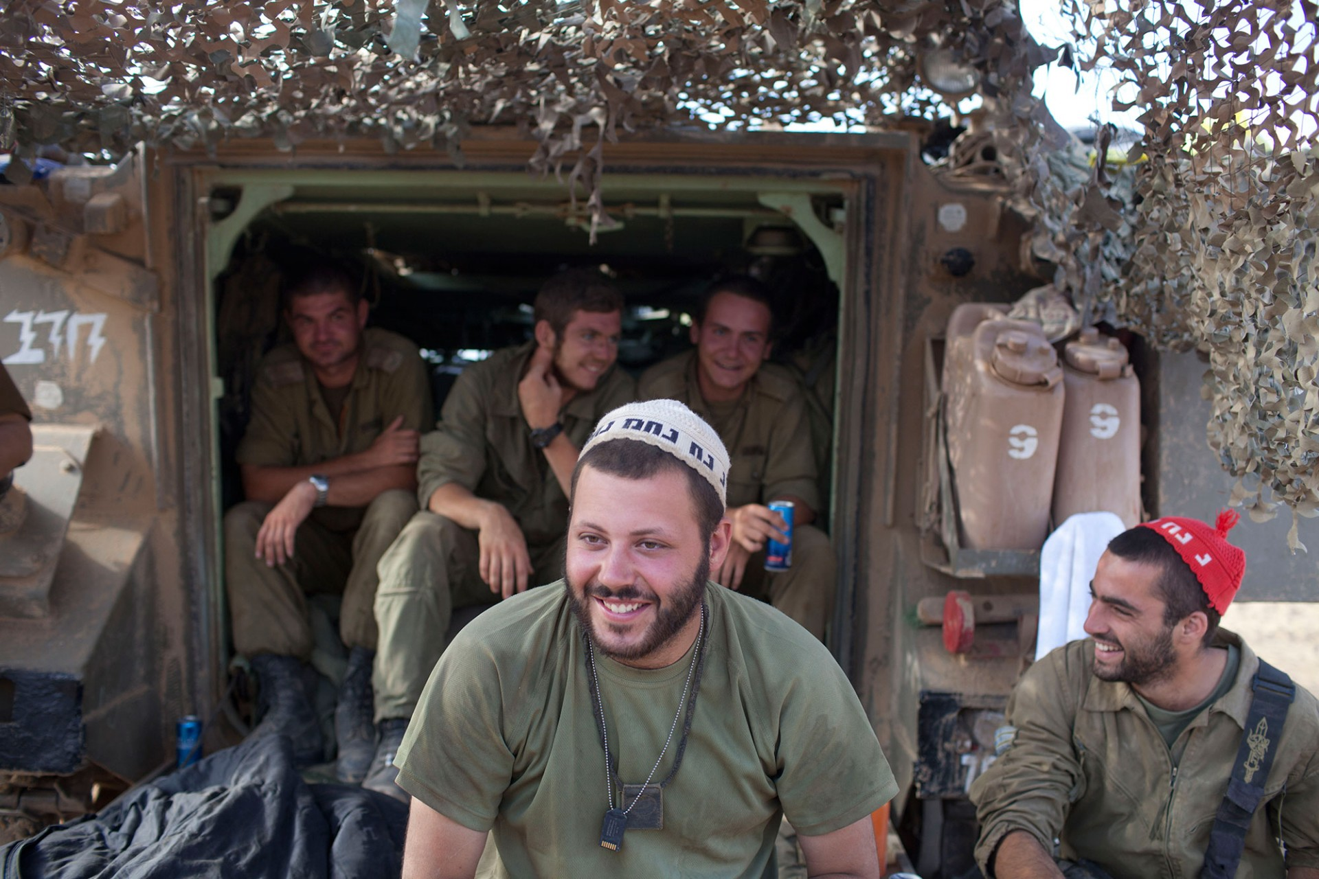 Israeli soldiers sit next to a Army Armoured Personnel Carrier (APC) in a deployment area on July 24, 2014 on Israel's border with the Gaza Strip.