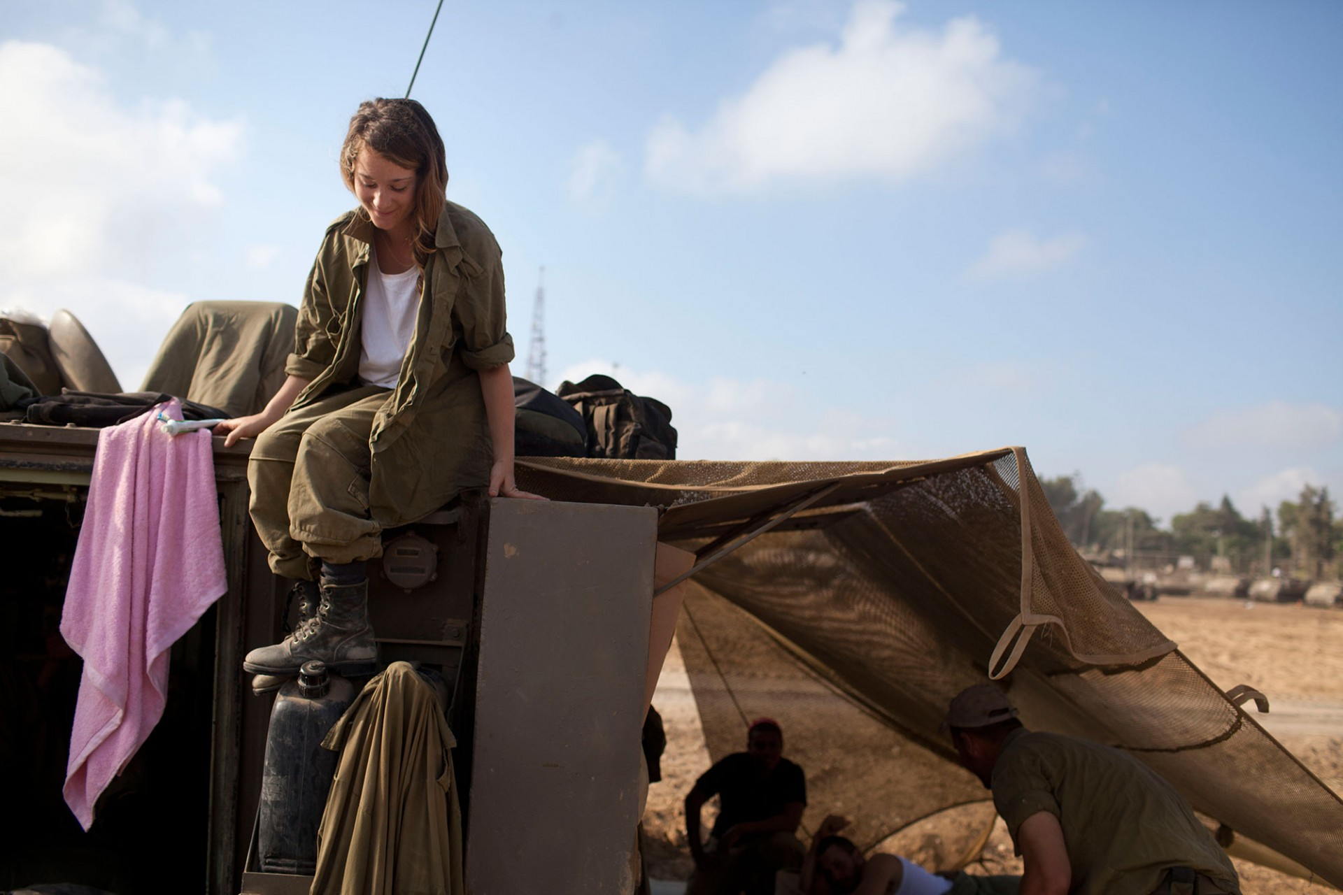An Israeli woman soldier sits on an Army Armoured Personnel Carrier (APC) in a deployment area on July 24, 2014 on Israel's border with the Gaza Strip.