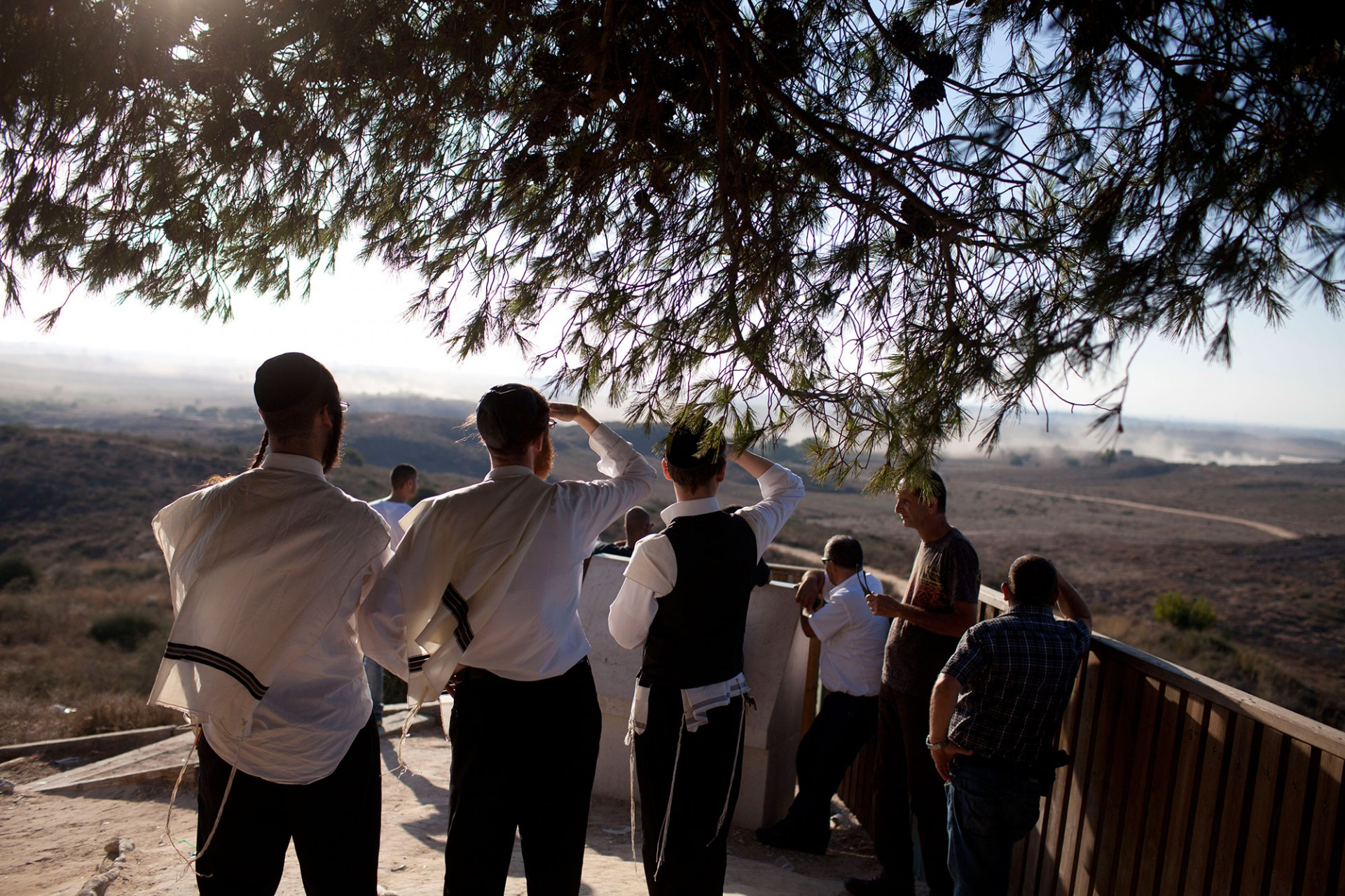 Ultra Orthodox Jews watch smoke plumes rises from Gaza on on July 24, 2014 on Israel's border with the Gaza Strip.